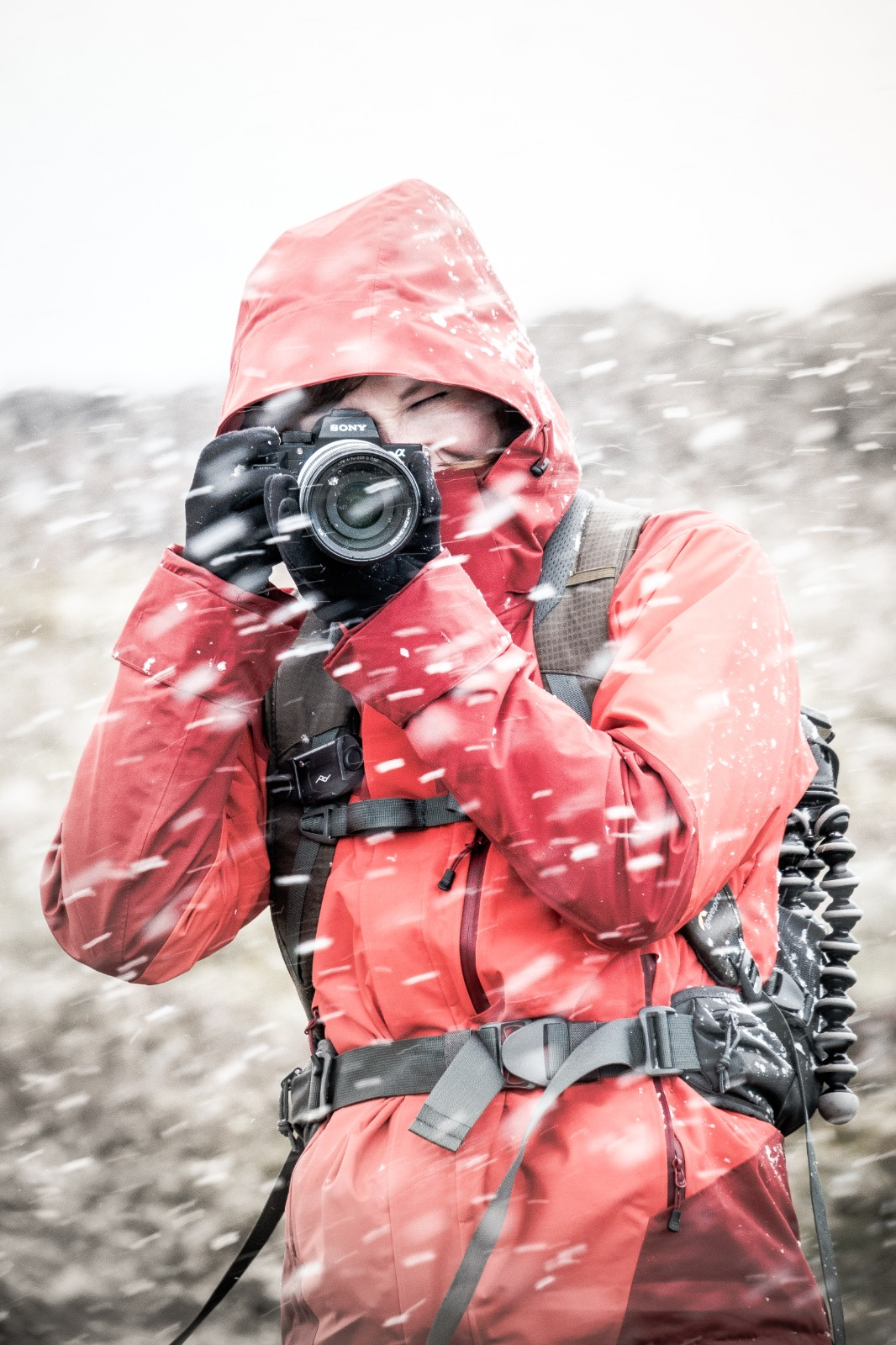 A photographer (Enna Bartlett) in a red coat stands with a camera to her eye while taking a picture in a snowstorm.